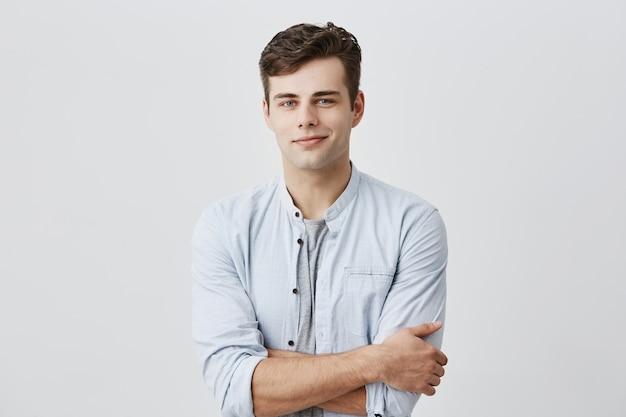 Bonito jovem europeu atraente na camisa casual, com cabelos escuros e olhos azuis, mantendo os braços cruzados, olhando com confiança com um sorriso agradável. expressão do rosto