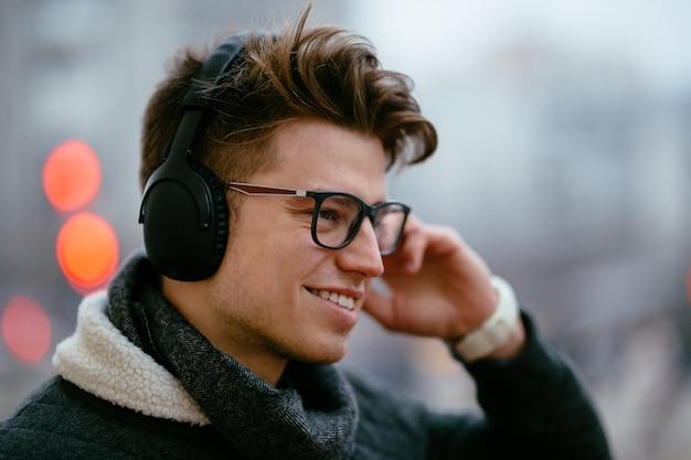 Bonito jovem feliz em óculos, ouvindo música em fones de ouvido