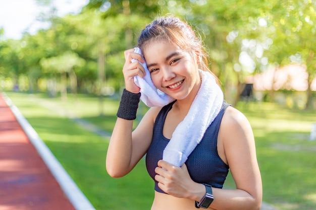 Bonito, jovem, feliz, mulher asian, usando, dela, branca, toalha, para, limpe, de, dela, suor, após, dela, corrida, e, exercício, em, a, manhã, em, um, pista corrente