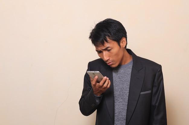 Bonito, jovem, homem asiático, com, curioso, verificar, seu, smartphone, desgastar, um, paleto, com, um, agasalho, i