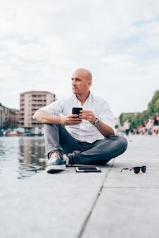 Bonito, jovem, homem negócios, em, um, camisa branca, sentada, por, a, água, usando, smartphone