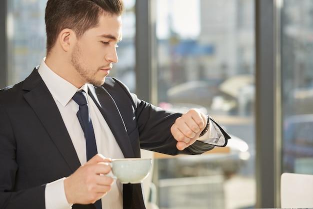 Bonito, jovem, homem negócios, verificar, tempo, ligado, seu, relógio, segurando, um, xícara café