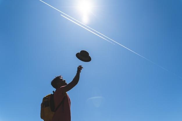 Bonito jovem indiano jogando chapéu para o céu.