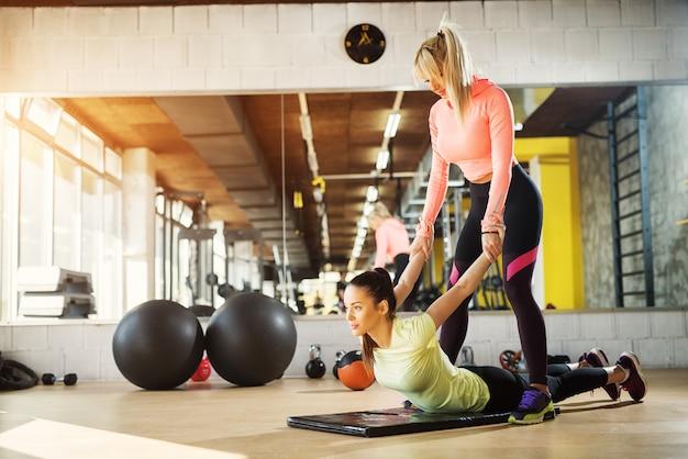 Bonito jovem instrutor feminino ajudando seu cliente a esticar os braços após treinamento duro em uma academia.