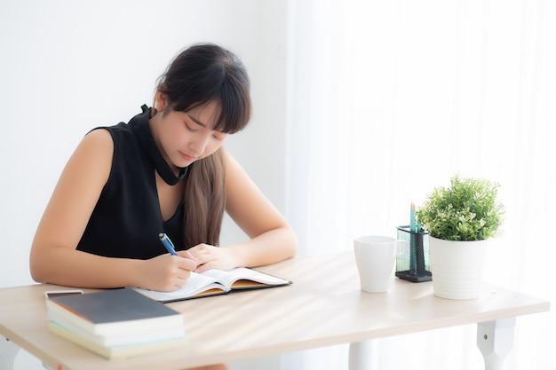Bonito, jovem, mulher asian, sorrindo, sentando, estudo, e, aprendizagem, escrita, caderno, e, diário, em, a, sala de estar