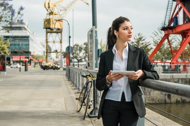 Bonito, jovem, mulher negócios fica, ligado, rua, segurando móvel, em, mão