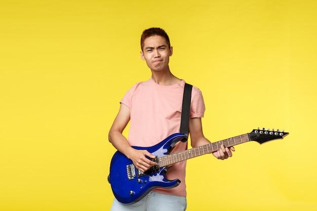 Bonito jovem músico tocando violão e cantando, isolado