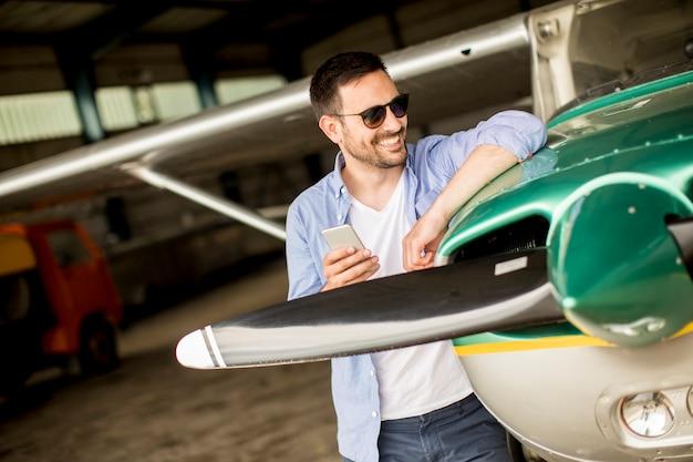 Bonito, jovem, piloto, verificar, avião, em, hangar, e, usando, telefone móvel