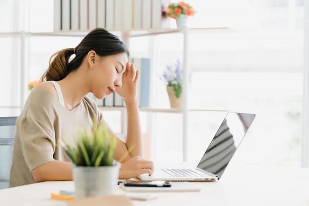 Bonito, jovem, sorrindo, mulher asian, trabalhando, laptop, escrivaninha, em, sala de estar, casa
