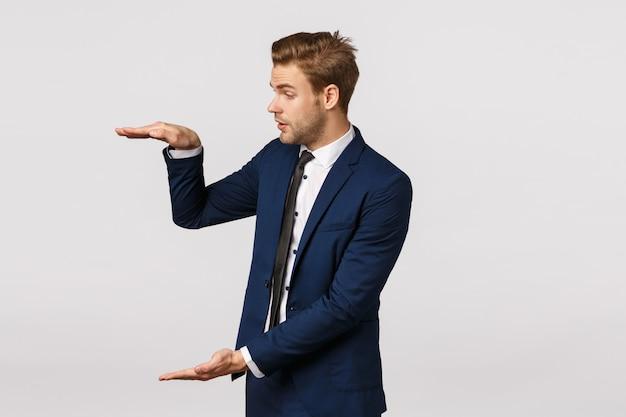Bonito loiro barbudo bonito impressionado no terno clássico azul, moldar grande objeto, falando sobre gráficos de negócios, discutir produtos grandes, segurando algo vasto