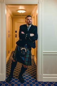 Bonito, maduro, corajoso, elegante, gay escocês de kilt em quarto de hotel chique