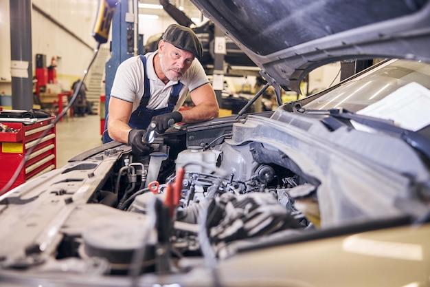 Bonito mecânico de automóveis trabalhando em uma oficina mecânica