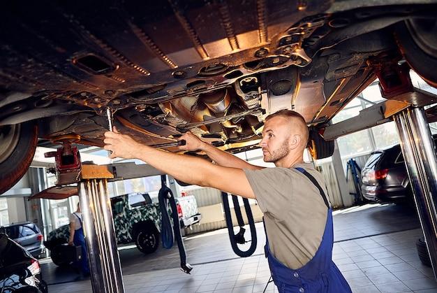 Bonito mecânico de automóveis verificando o rolamento do automóvel na estação de serviço.