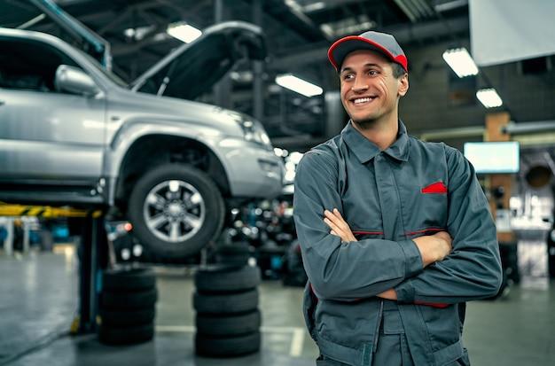 Bonito mecânico de serviço automático de uniforme está de pé no fundo do carro com o capô aberto, sorrindo e olhando para longe. reparação e manutenção de automóveis.