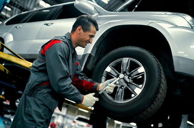 Bonito mecânico de uniforme está trabalhando no serviço automotivo. reparação e manutenção de automóveis. segurando a roda do carro.