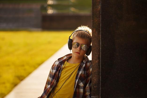 Bonito, menino adolescente, escutar música, e, usando, telefone, ligado, pôr do sol