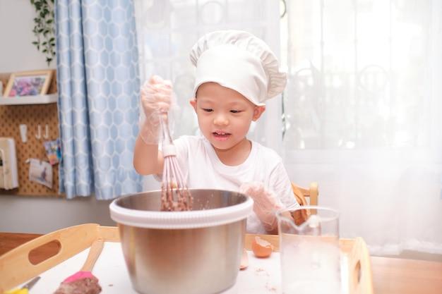 Bonito menino asiático de 4 anos de idade se divertindo preparando bolo ou panquecas, aproveite o processo mistura a massa usando o batedor em casa
