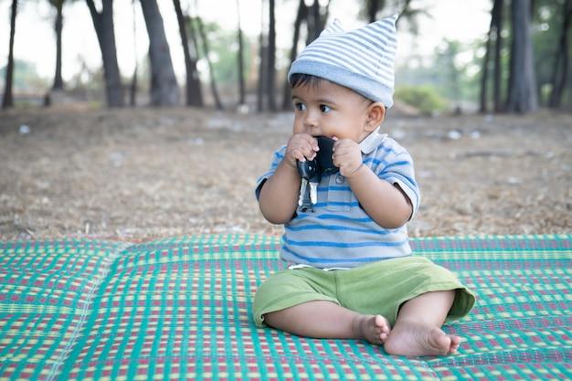 Bonito menino asiático sentado no parque