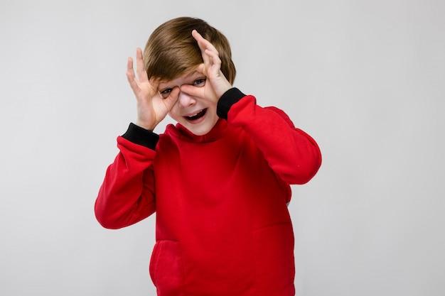 Bonito menino caucasiano confiante na camisola vermelha, mostrando o gesto engraçado na parede cinza