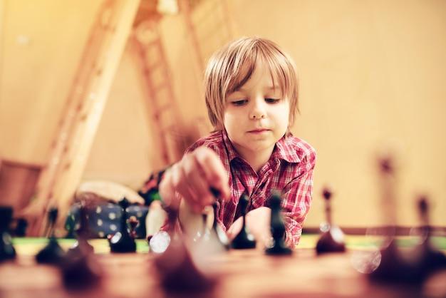 Bonito menino pré-escolar está jogando xadrez em casa