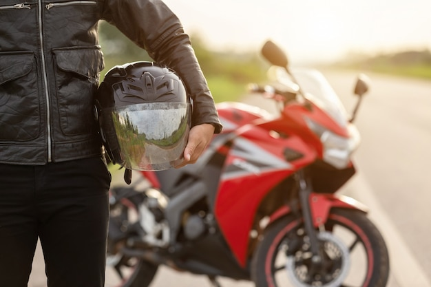 Bonito, motociclista, desgaste, casaco couro, segurando, capacete, estrada