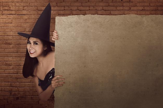 Bonito, mulher asian, com, chapéu, e, bruxa, traje, escondendo, e, auge, forma, atrás de, em branco, pergaminho