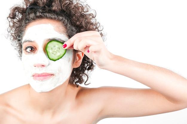 Bonito, mulher jovem, com, máscara rosto, segurando, pepino, fatia, sobre, dela, olho
