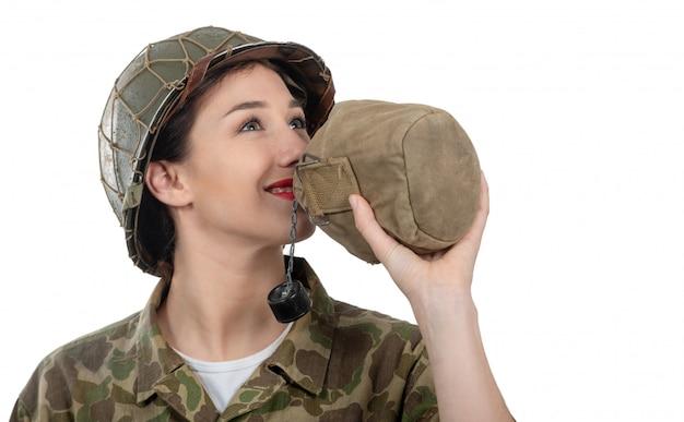 Bonito, mulher jovem, em, ww2, americano, uniforme, bebendo, água