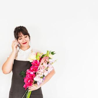 Bonito, mulher jovem, falando telefone móvel, segurando, grupo flores