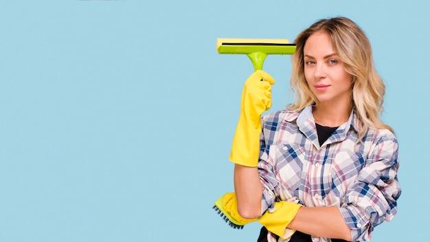 Bonito, mulher jovem, segurando, plástico, limpador, ficar, frente, azul, superfície