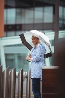 Bonito, mulher segura, guarda-chuva, e, ficar, ligado, rua