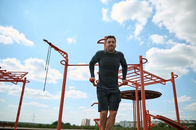 Bonito musculoso construído desportista caucasiano europeu maduro malhando na barra transversal ao ar livre em sportsground de verão. conceito de estilo de vida ativo e saudável, exercícios ao ar livre, fitness e musculação