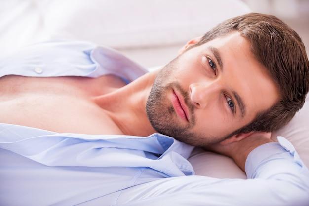 Bonito na cama. vista superior de um jovem bonito com uma camisa desabotoada, segurando a mão atrás da cabeça e olhando para a câmera enquanto está deitado na cama
