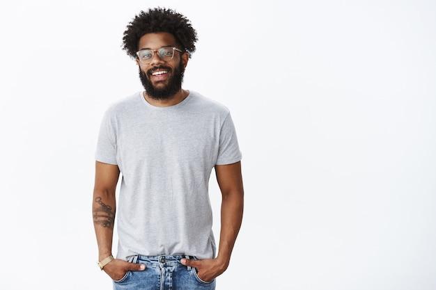 Bonito namorado afro-americano de aparência amigável, satisfeito e feliz, de óculos, com piercing no nariz e tatuagens no braço, sorrindo alegremente e segurando as mãos nos bolsos, tendo uma conversa agradável