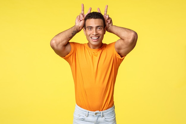 Bonito namorado hispânico masculino e bobo em camiseta laranja, faça o gesto de paz, orelhas de coelho atrás da cabeça, sorrindo alegremente, mimick coelho para brincar com a sobrinha sobre fundo amarelo