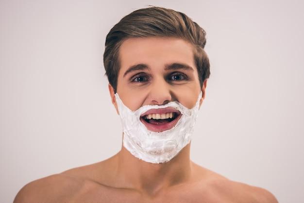 Bonito nu jovem com espuma de barbear no rosto