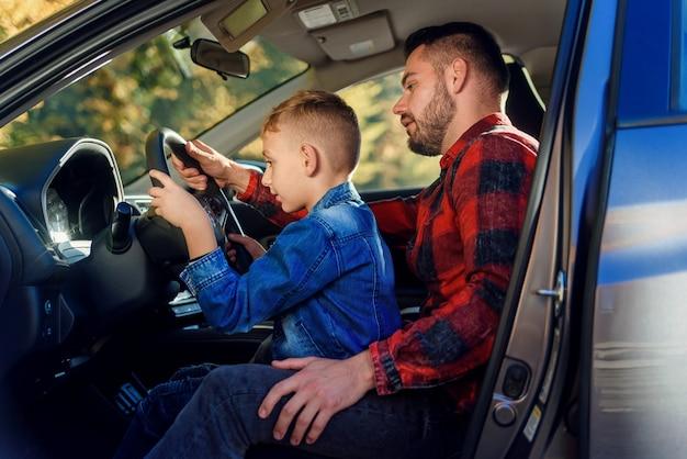 Bonito pai apontando algo enquanto ensinava filho adolescente dirigindo carro