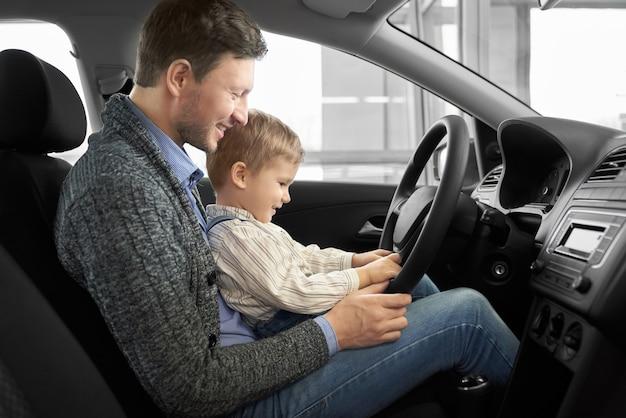 Bonito pai com filho sentado no banco do motorista em carro novo