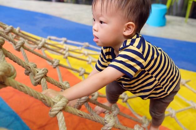 Bonito pequeno asiático 2 anos de idade criança bebê menino se divertindo tentando subir no trepa-trepa no playground indoor, física, coordenação de mãos e olhos, sensoriais, conceito de desenvolvimento de habilidades motoras