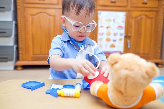 Bonito pequeno asiático 2 anos de idade criança menino criança brincando de médico com brinquedos de pelúcia em casa, garoto segurando o estetoscópio examinar o ursinho de pelúcia brinquedo