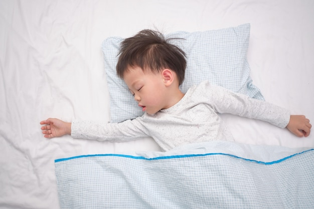 Bonito pequeno asiático 3-4 anos de idade criança menino criança de pijama, tirando uma soneca, dormindo de costas no lençol branco na cama