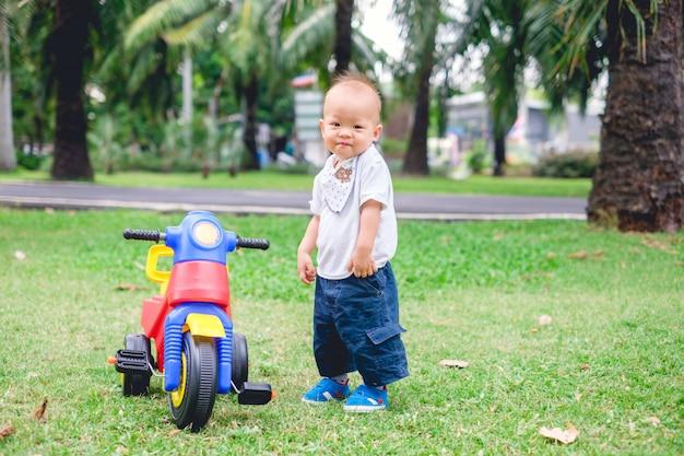 Bonito pequeno bebê asiático menino montando seu triciclo no parque de verão