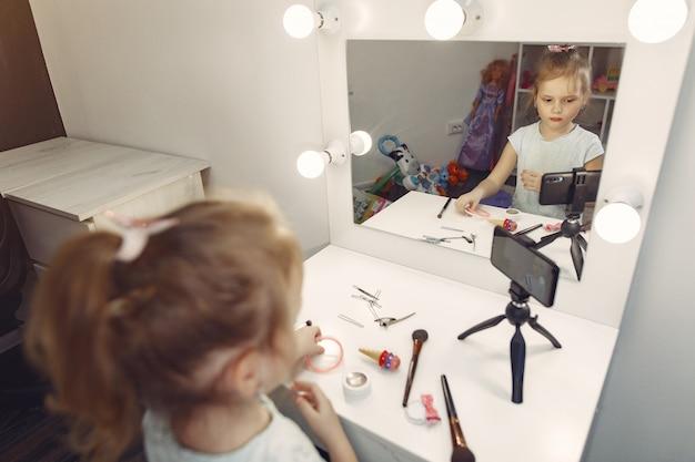 Bonito pequeno blogueiro com cosméticos, gravação de vídeo em casa