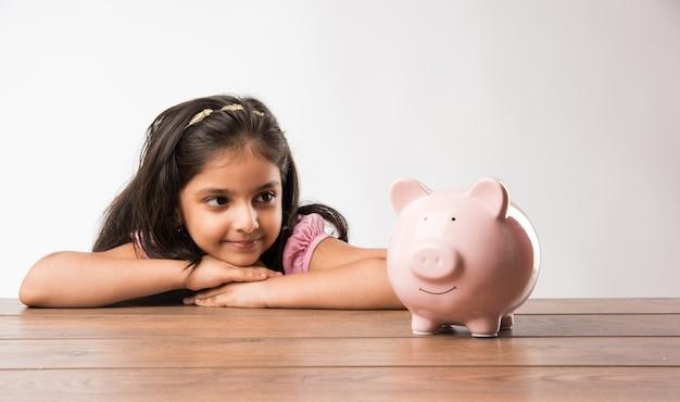 Bonito pequeno indiano ou asiático com cofrinho, colocando moedas, ou pensando ou mostrando os polegares. planejando para o futuro