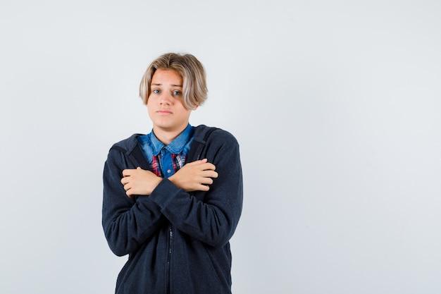 Bonito rapaz adolescente abraçando a si mesmo ou sentindo frio na camisa, moletom com capuz e parecendo indefeso. vista frontal.