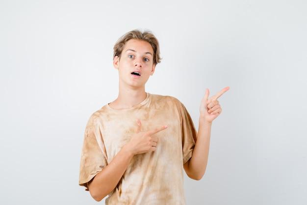 Bonito rapaz adolescente apontando para o canto superior direito da t-shirt e parecendo perplexo. vista frontal.