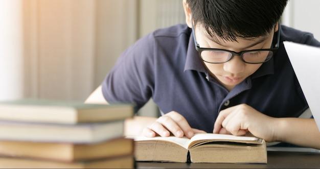 Bonito rapaz adolescente asiático fazendo sua lição de casa em casa.