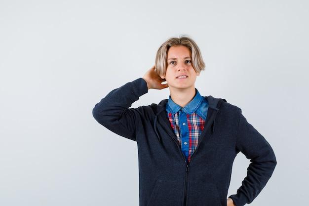 Bonito rapaz adolescente com a mão atrás da cabeça, olhando para cima na camisa, moletom e olhando pensativo, vista frontal.