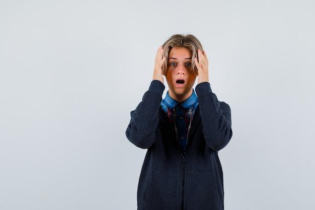 Bonito rapaz adolescente com as mãos perto da cabeça na camisa, moletom com capuz e parecendo agitado. vista frontal.
