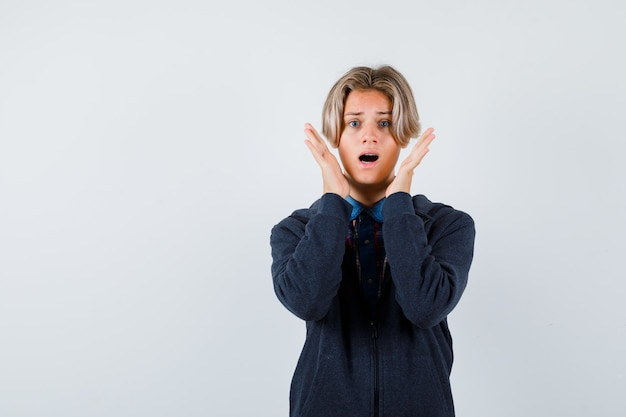 Bonito rapaz adolescente com as mãos perto do rosto na camisa, moletom com capuz e parecendo agitado. vista frontal.